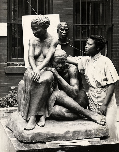 Augusta Savage posing with her sculpture Realization