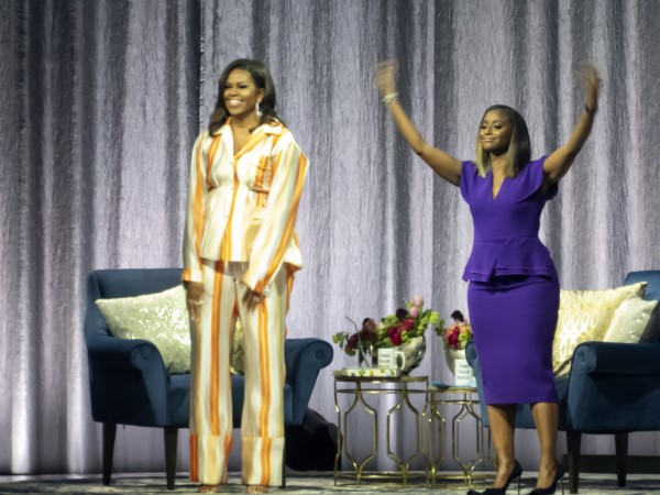 Isha Sesay waves her arms as crowd greets Michelle Obama